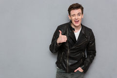 Man in leather jacket showing thumb up and winking. Portrait of a young man in leather jacket showing thumb up and winking on gray background Royalty Free Stock Photo