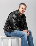 Man in leather jacket sitting on chair Royalty Free Stock Photography
