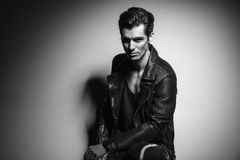 Man in leather jacket sitting and leaning elbow on knee Royalty Free Stock Photo