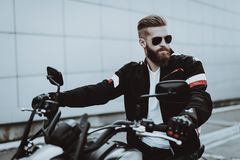 Biker In A Sunglasses Is Sitting On Motorcycle. Man In Leather Jacket Is Sitting On Motorcycle. Going For Ride. Fashion Rider. Confident Stare. Speed Vehicle royalty free stock image