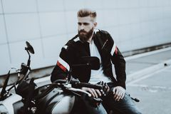 Man In Leather Jacket Is Sitting On Motorcycle. Going For Ride. Fashion Rider. Confident Stare. Speed Vehicle. Cool Biker With A Beard. Motorbike Concept royalty free stock photo