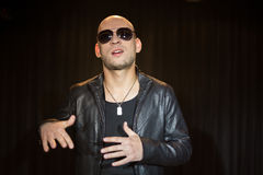 A man in a leather jacket with sunglasses. Gesturing with his hands royalty free stock image