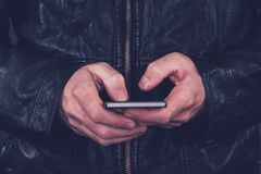 Man in leather jacket using mobile phone. For texting. Modern technology and lifestyle concept Royalty Free Stock Photos