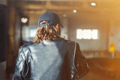 Man in leather jacket. A young man in a leather jacket and cap on the back Stock Image