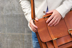 Man with leather shoulder bag. Cropped portrait of man with leather shoulder bag, focus on hands Stock Photo