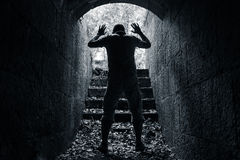 Man leaves dark stone tunnel with raised hands. Surrender concept black and white photo Royalty Free Stock Photography