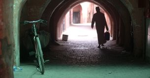 A man leaves his bicycle and passes into the tunnel of the old town. The emotions between perfumes and colors in the eastern markets in the old city market Stock Image