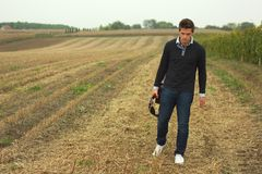 Man leaving field. Young man with guitar leaving field stock photo