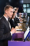 Man at lectern. Man in suit standing at lectern with microphone stock photography