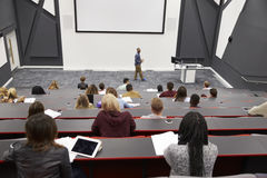 Man lectures students in lecture theatre, back row seat POV Royalty Free Stock Photography