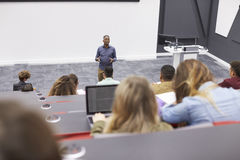 Man lectures students in lecture theatre, back row seat POV Royalty Free Stock Photos