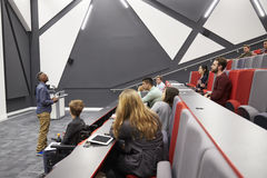 Man lectures students in lecture theatre, front row seat POV Stock Photo