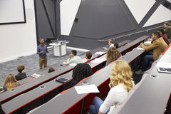 Man lectures students in lecture theatre, mid row seat POV Royalty Free Stock Images