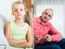 Man lecturing unpleased little girl Stock Photos