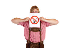 Man in lederhose holds no-smoking-rule sign Stock Photo