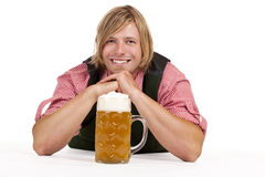 Man with lederhose and oktoberfest beer stein. Lying on floor. Isolated on white background Royalty Free Stock Photos