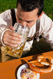 Man in Lederhosen drinking beer royalty free stock photography