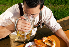 Man in Lederhosen drinking beer Royalty Free Stock Image