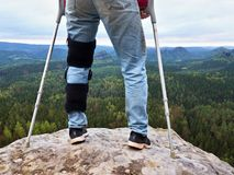 Man with leg in knee cages and crutches for stabilization stay on rock. Hurt tourist walk in mountains. Drama view bellow into valley Stock Image
