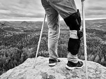 Man with leg in knee cages and crutches for stabilization stay on rock. Hurt tourist walk in mountains. Drama view bellow into valley Stock Images