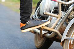 Man leg with shoe over the bike stock image