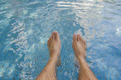 Man legs at blue water of swimming pool Stock Photos