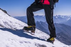 Man legs in crampons come to the top of mountain. Feet in trekking boots on the background of the Caucasus. Man legs in crampons come to the top of mountain Royalty Free Stock Photos