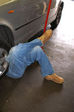 Man With Legs Crossed Working Under a Car Royalty Free Stock Photo