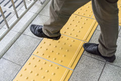 Man legs are crossing the yellow line on the train station Stock Images