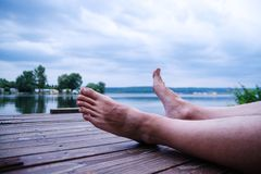 Man legs on a dock while relaxing on seaside. Royalty Free Stock Photo