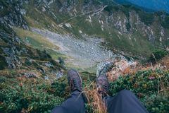 Man legs, sitting on edge of gorge. Point of view, focus on background, Carpathian mountains, Marmarosh royalty free stock photo