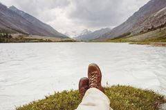 Man legs lake rest mountains view. Closeup photo of tourist`s legs against mountains valley and lake. Active tourism concept Stock Images