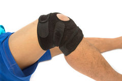 Man legs with one knee in a protective knee brace Stock Images