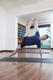 Man with legs raised and arms outstretched doing yoga in a yoga studio Royalty Free Stock Images