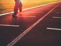 Man legs in running shoes  on red racetrack on outdoor stadium. Stock Images