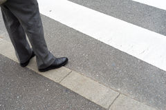 Man legs in slag pants waiting to cross the street at a crosswal Stock Images