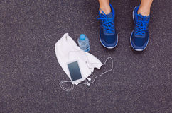 Man legs with sneakers, towel, water and. Top view of man legs with sneakers, towel, water bottle and smartphone with earphones over a dark gym floor background Stock Photography