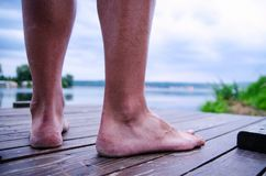 Man legs standing on a dock while relaxing on seaside. Stock Photos