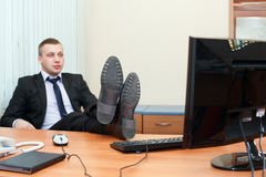 Man with legs on table in office Stock Images
