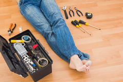 Man legs with toolbox on floor at home Stock Photo