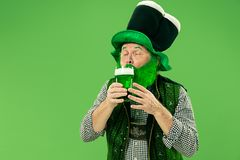 A man in a leprechaun hat at studio. He celebrates St. Patrick`s Day. A smiling happy senior man in a leprechaun hat with green beer at studio. He celebrates St stock image