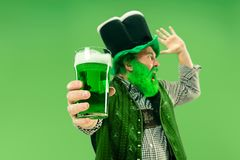 A man in a leprechaun hat at studio. He celebrates St. Patrick`s Day. A smiling happy senior man in a leprechaun hat with green beer at studio. He celebrates St stock photography