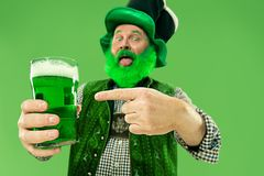 A man in a leprechaun hat at studio. He celebrates St. Patrick`s Day. A smiling happy senior man in a leprechaun hat with green beer at studio. He celebrates St royalty free stock image