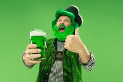 A man in a leprechaun hat at studio. He celebrates St. Patrick`s Day. A smiling happy senior man in a leprechaun hat with green beer at studio. He celebrates St stock photos