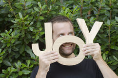 Man with letters of the word joy. Man hiding behind the wooden letters of the word joy Stock Image
