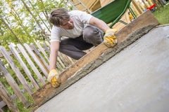 Man leveling the cement in a backyard at home using a wooden pla. Nk as he lays a new concrete surface, low angle tilted view Stock Photos