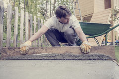 Man leveling the cement in a backyard. Retro effect faded and toned image of a man leveling the cement in a backyard at home using a wooden plank Stock Images