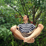 Man levitating in garden. Handsome levitating man in a leafy garden evoking peace, confidence and tranquility Stock Photo