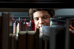 Man in Library. Young man browsing through the racks of books in a library Royalty Free Stock Photography
