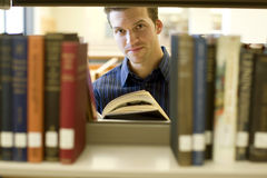 Man at library. Happy young man researching info at a library Stock Photos